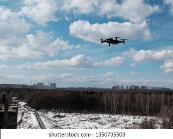 UAV drone copter hovering in the bright blue sky with clouds above forest and city blocks at the background