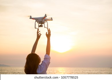 The UAV drone and photographer woman hands.drone copter flying with digital camera. UAV Drone with digital camera. Flying camera take a photo and video.The drone with camera takes pictures of the sky.
