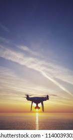 UAV drone quadcopter with digital camera in the sunrise sky. Close up of quadrocopter outdoors.