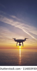 UAV drone quadcopter with digital camera in the sunrise sky. Close up of quadrocopter outdoors.