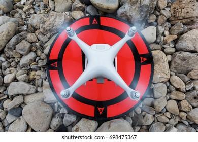 UAV, Quadcopter hovering above landing pad
