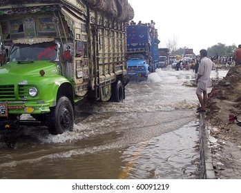 UBAURO, PAKISTAN - AUG 30: Vehicles pass through flood water at a National  Highway due to a break of Bhong Bund at Kot Subzal on August 30, 2010 in Ubauro.