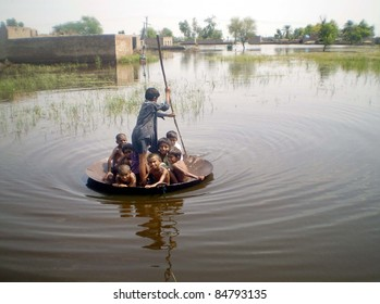 UBAURO, PAKISTAN - SEPT 16: Rain-affected unidentified children travel at a flood hit area while inundated houses also seen in picture in Ubauro September 16, 2011.