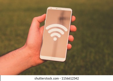 Ubeda, Spain - August 11, 2018: Holding an LG G6 Android smartphone on hand with a WiFi icon shown on screen
