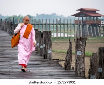 Ubein bridge, Amarapura, Myanmar.- November9, 2019: Myanmar nun carrying shoulder bag ,walking on Ubein bridge, Myanmar in sunrise time on november9, 2019.