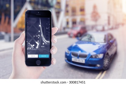 Uber application startup page on the Apple iPhone 5s display in female hand. Blurred street view with car and flare sun light on the background. Varna, Bulgaria - May 25, 2015.