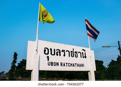UBN, Thailand - March 14, 2014: Ubonratchatani railway station sign with Thai and 60th reigning celebrated flag on blue clear sky.