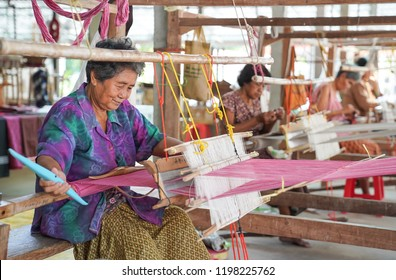 Ubon Ratchathani, Thailand - October 6, 2018: Old Thai woman was weaving traditional cotton cloth.