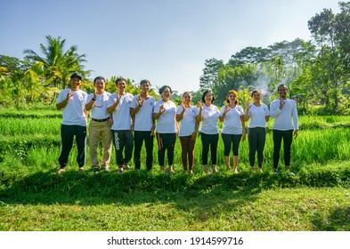 Ubud, Bali, Indonesia - 21 June 2019: Group of people posing namaste and ok at a rice field in Bali, in the morning.