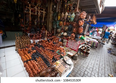 Ubud, Bali / Indonesia - December 26 2017: A stand of small handcrafted wooden statues at the market of Ubud