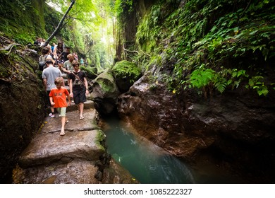 Ubud, Bali / Indonesia - December 29 2017: Tourists walking on a narrow path in the Monkey Forest of Ubud