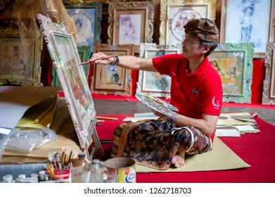 Ubud, Bali / Indonesia - February 18, 2012 - a male painter working on his painting.