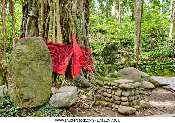 Ubud, Bali, Indonesia - January, 2020: Macaque monkeys and statues at Ubud Bali, Indonesia. Sacred Monkey Forest and Hindu temple complex in Ubud.
