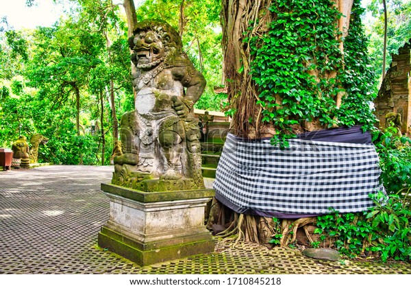 Ubud, Bali, Indonesia - January, 2020Macaque monkeys and statues at Ubud Bali, Indonesia. Sacred Monkey Forest and Hindu temple complex in Ubud.