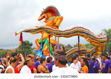 UBUD, BALI, INDONESIA - March 17, 2018. Balinese men are walking in procession with giant scary dragon doll at New Years Eve, Nyepi Silent Day celebrations..