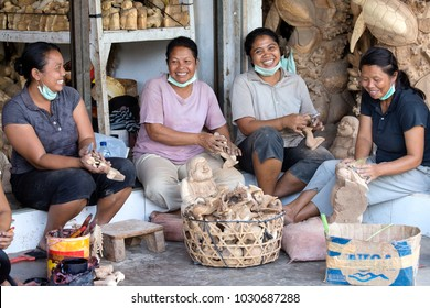 UBUD, BALI, INDONESIA - MARCH 23, 2015 : Unidentified women are making wooden souvenirs for tourists. Woodcarving is a traditional handicraft in Bali, Indonesia