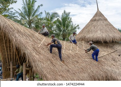 UBUD, BALI, INDONESIA - MARCH 24, 2019 : Local men fixing a new straw roof in Ubud, island Bali, Indonesia. Construction workers working on a building thatch roof