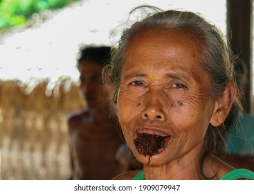 Ubud, Bali (Indonesia) - March, 25. 2008: Portrait colose up of aged old balinese indonesian woman chewing a piece of raw loose tobacco (focus on woman)