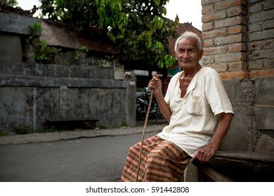UBUD, BALI, INDONESIA - NOV 7, 2013: Old local man with bamboo cane sits on stone bench.
