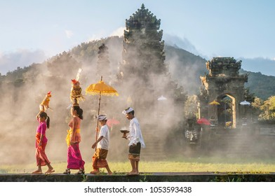 Ubud, Bali - July 30, 2016. Illustrative Editorial. Showing traditional Balinese male and female ceremonial clothing and religious offerings, as a mother and children walk to a Hindu temple (pura).