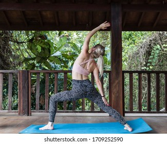 Ubud, Gianyar / Bali Indonesia - Circa October 2019: Young woman practicing Yoga in Bali surrounded by jungle.