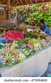 UBUD, INDONESIA - AUGUST 29, 2008: Woman preparing traditional sacred fruits for ritual in hinduism