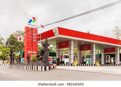 UBUD, INDONESIA - January 26, 2013.  Petrol station employee fills bike with gas. Pertamina gas station.
