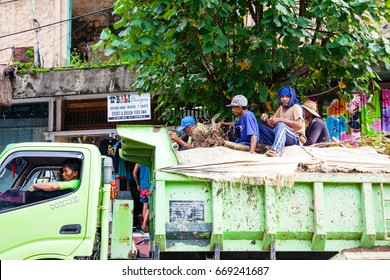 UBUD, INDONESIA - MARCH 2: Workers rides in the back of the truck on March 2, 2014 in Ubud, Indonesia.
