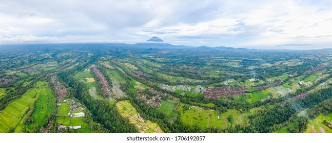 Ubud location aerial panoramic shot and view to Agung volcano on the horizon. Green fields and hills between the villages and rice terraces. Cloudy weather. Tropical and relax concept.