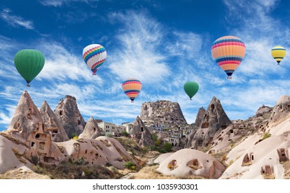 Uchhisar fortress and colorful hot air balloons flying over Pigeon valley in Cappadocia, Anatolia, Turkey