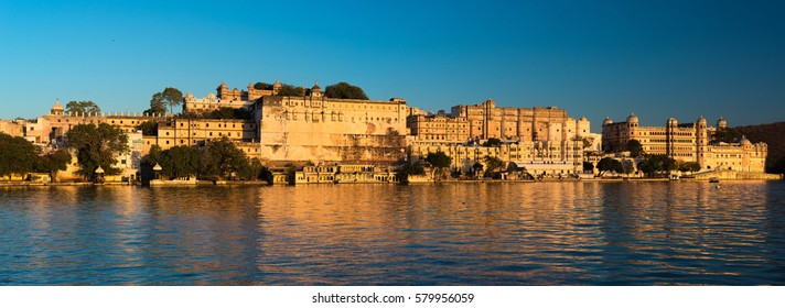 Udaipur cityscape at sunset. The majestic city palace on Lake Pichola, travel destination in Rajasthan, India.