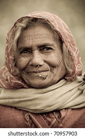 UDAIPUR, INDIA - CIRCA JANUARY 2007: An old Indian woman with traditional nose-ring smiles in the fields circa January 2007 in Udaipur, India.