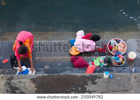 UDAIPUR, INDIA - JANUARY 16, 2015 : Aerial view of two women washing clothes on the steps of Lal Ghat next to Lake Pichola.