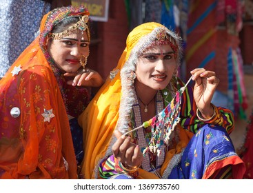 UDAIPUR, INDIA - JANUARY 7, 2019: Indian Rajasthani women in traditional clothes selling beads at local market, Rajasthan state