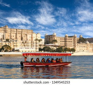 UDAIPUR, INDIA - JANUARY 8, 2019: Tourists in wooden boat floating on Pichola lake along Udaipur City Palace Complex in Rajasthan, India