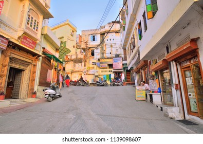 Udaipur, India - November 13, 2017: Colorful streets in Udaipur with shops and motorbikes on the side of the road.