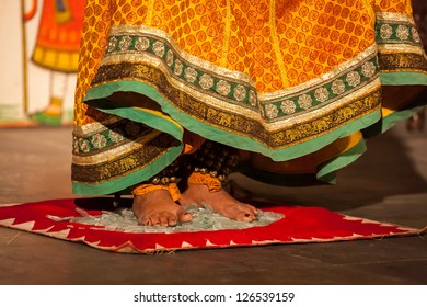 UDAIPUR, INDIA - NOVEMBER 24: Bhavai performance - folk dance of Rajasthan Performer balances number of pots as she dance on broken glass. Legs close up. November 24, 2012 in Udaipur, Rajasthan, India