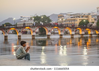 Udaipur, Rajasthan / India - 06 03 2018: A Indian boy sitting with his smart phone by the city lake at sunset with a small walking bridge in the background.