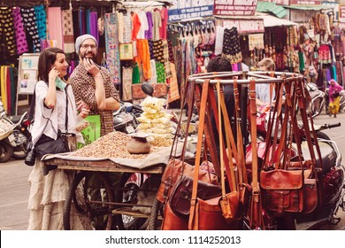 Udaipur, Rajasthan, India, Feruary 6, 2018: European tourist couple buying nuts from the street seller
