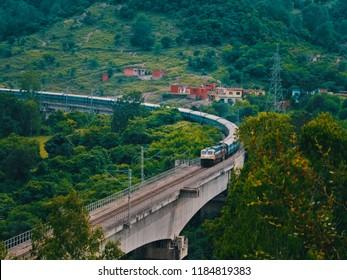 Udhampur, Jammu and Kashmir, India - September 15, 2018: 16031 Chennai Central - Shri Mata Vaishno Devi Katra Andaman Express crossing a viaduct near Udhampur.