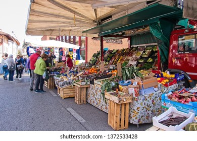 Udine, Italy - April 2 2019 :People at the local traditional outdoor market. Vegetable and fruit stand.