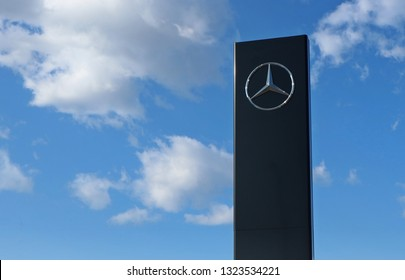 Udine, Italy. February 22 2019. Mercedes Benz logo in the car dealership of the area, against a blue  sky  with clouds. It is the symbol of the   multinational luxury car manufacturer