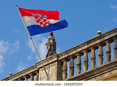Udine, Italy. June 13, 2019. Croatia flag on a balcony with a decorative statue, against a blue sky background
