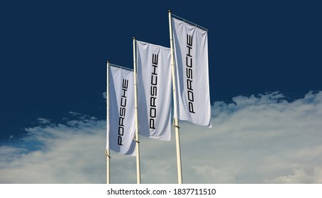 Udine, Italy. October 18 ,2020. Porsche flags waving outside the local dealer of the german luxury automaker under a blue  sky with clouds