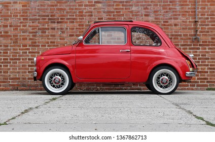 Udine,Italy. April 12 2019. An iconic vintage red Fiat 500 recently restored on brick wall background