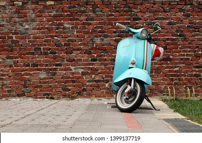 Udine,Italy. May 14 2019. An iconic vintage blue Vespa scooter parked. Old brick wall on background