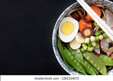 Udon noodle soup with fresh snow peas, carrots, spring onions and egg.  Flat lay with copy space.