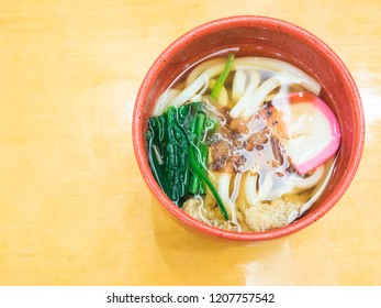 Udon noodles (Kake udon). A bowl of Japanese noodle soup topped with sliced kamaboko, dashi, and spinach. Top view on wooden background