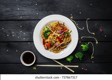 Udon stir fry noodles with chicken and vegetables in a white plate on black wooden background. With chopsticks and sauce