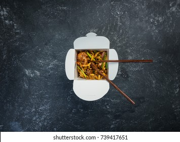 Udon stir fry noodles with chicken in a box on a vintage colored background. Top view. With chopsticks